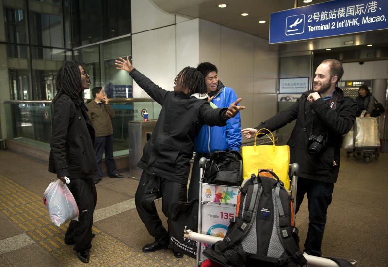 American rappers from left, Pacman and Peso, dance next to their crew members at the Beijing Capital Airport in Beijing, China Saturday, Nov. 30, 2013. Pacman and Peso, whose real names are Anthony Bobb and Dontray Ennis ended their trip to North Korea on Saturday arrived in Beijing, after spending five days in North Korea to film their music video, which funded by Kickstarter campaign. (AP Photo/Andy Wong)