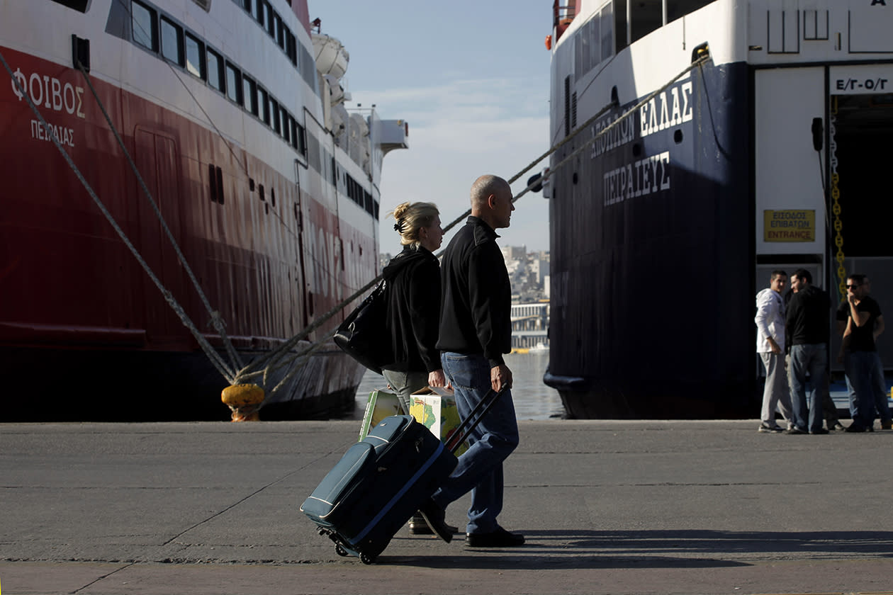 Tourists carry their luggage as their pass in front of docked ships at the port of Piraeus, near Athens during a 48-hour nationwide general strike.