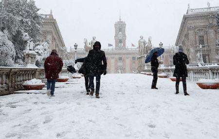 People walk at the Campidoglio palace during a heavy snowfall in Rome, Italy February 26, 2018. REUTERS/Remo Casilli