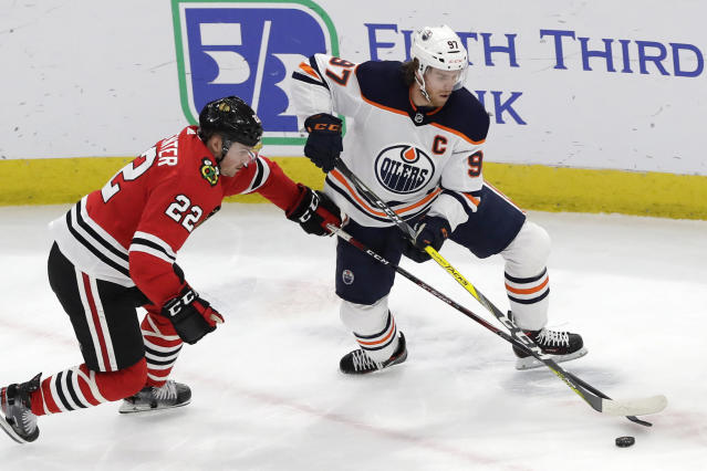 Edmonton Oilers center Connor McDavid, right, and Chicago Blackhawks center Ryan Carpenter battle for the puck during the first period of an NHL hockey game in Chicago, Thursday, March 5, 2020. (AP Photo/Nam Y. Huh)