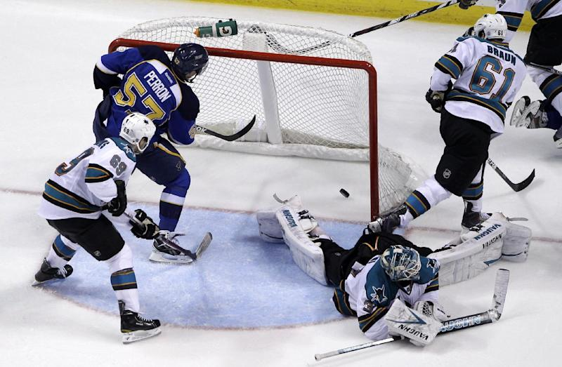 St. Louis Blues' David Perron (57) scores past San Jose Sharks goalie Antti Niemi, of Finland, Andrew Desjardins (69) and Justin Braun (61) during the third period in Game 2 of an NHL Stanley Cup first-round hockey playoff series Saturday, April 14, 2012, in St. Louis. The Blues won 3-0. (AP Photo/Jeff Roberson)