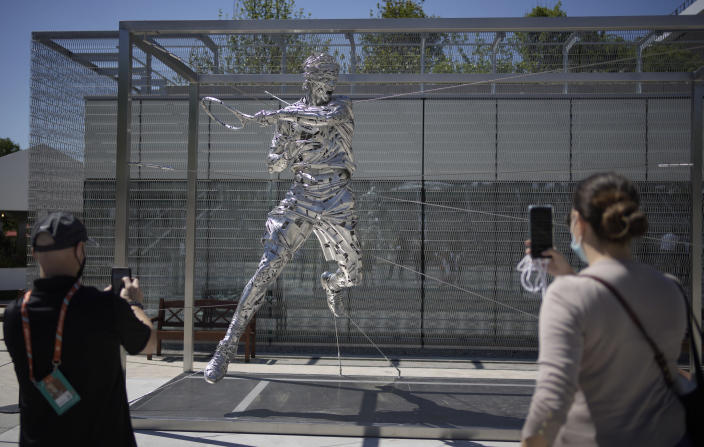 Spectators take photos on their smartphones of a new statue of Spain's Rafael Nadal on day two of the French Open tennis tournament at Roland Garros in Paris, France, Monday, May 31, 2021. (AP Photo/Christophe Ena)