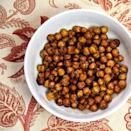 """<p>High in protein and fiber, chickpeas offer a satisfying crunch when roasted. Just swap the honey for maple syrup to make this snack vegan. </p> <p><strong>Get the recipe:</strong> <a href=""""https://www.popsugar.com/fitness/Roasted-Honey-Cinnamon-Chickpeas-27908653"""" class=""""link rapid-noclick-resp"""" rel=""""nofollow noopener"""" target=""""_blank"""" data-ylk=""""slk:roasted honey cinnamon chickpeas"""">roasted honey cinnamon chickpeas</a></p>"""