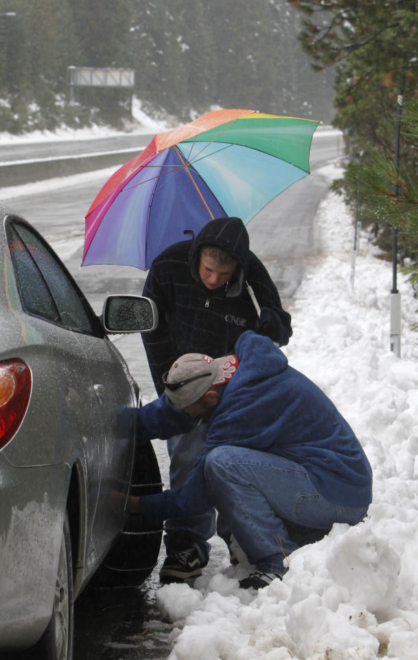 Jeff Kirsch, 15, uses an umbrella to provide his father, Robert, some protection from the snow as he installs snow chains on the family car near Nyack, Calif, Monday, Oct. 22, 2012. The first storm of the season swept through Northern California bringing rain to the lower elevations and snow in the mountains. (AP Photo/Rich Pedroncelli)
