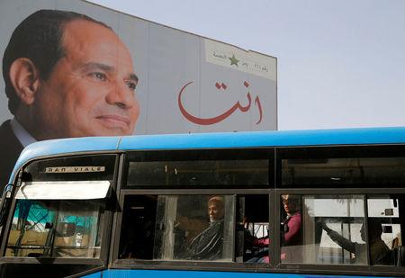 FILE PHOTO: People ride on a bus as posters with Egypt's President Abdel Fattah al-Sisi are displayed during preparations for the presidential election in Cairo
