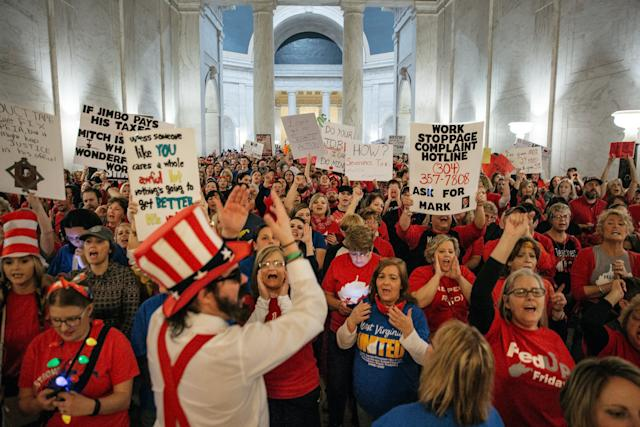 Striking school workers hold signs and chant inside the West Virginia Capitol in Charleston, March 2, 2018.