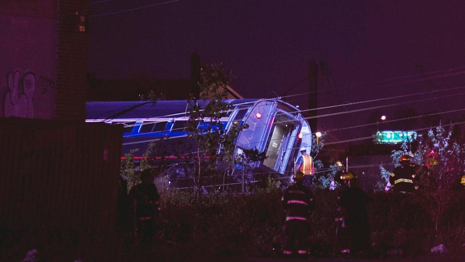 Rescue workers survey the wreckage after an Amtrak passenger train derailed in Philadelphia, Pennsylvania May 12, 2015. The Amtrak passenger train with more than 200 passengers on board derailed in north Philadelphia on Tuesday night, killing at least five people and injuring more than 50 others, several of them critically, authorities said. Authorities said they had no idea what caused the train wreck, which left some demolished rail cars strewn upside down and on their sides in the city's Port Richmond neighborhood along the Delaware River. REUTERS/Charles Mostoller