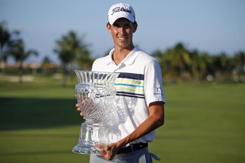 U.S. Chesson Hadley poses for pictures with his Puerto Rico Open PGA golf trophy after winning the tournament in Rio Grande, Puerto Rico, Sunday, March 9, 2014. (AP Photo/Ricardo Arduengo)