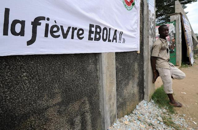 A man stands near a banner reading ''Ebola fever!!'' '' prior to a football tournament gathering youth from Guinea near the Koumassi sports center in Abidjan on August 10, 2014 (AFP Photo/Sia Kambou)