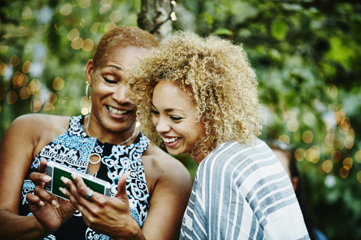 Smiling mature aunt showing niece photos on smartphone during party in backyard of home