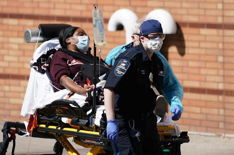 "Emergency Medical Technicians bring a patient into Wyckoff Hospital in the Borough of Brooklyn on April 6, 2020 in New York. - New York Governor Andrew Cuomo on Monday extended a shutdown in the epicenter of America's deadly coronavirus pandemic until near the end of the month. Cuomo said the COVID-19 death rate in New York was ""effectively flat"" for the past two days but announced that schools and non-essential businesses must stay shut until April 29. (Photo by Bryan R. Smith / AFP) (Photo by BRYAN R. SMITH/AFP via Getty Images)"