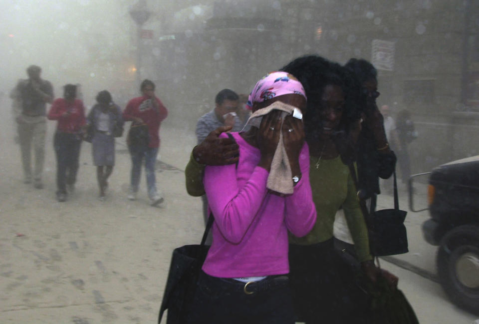 People cover their faces as they escape the collapse of New York's World Trade Center on Sept. 11, 2001. (AP Photo/Suzanne Plunkett)