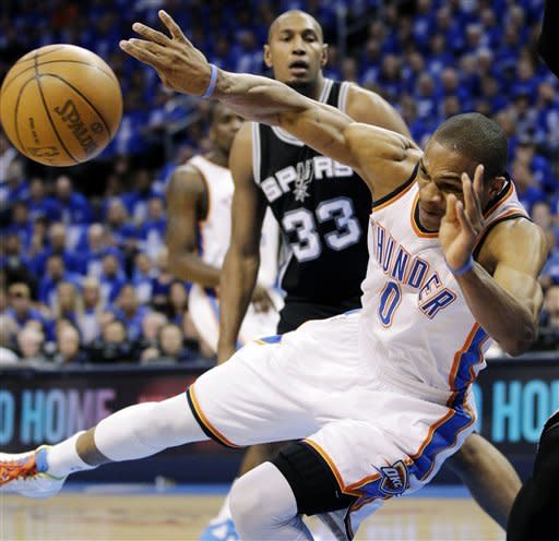 Oklahoma City Thunder point guard Russell Westbrook (0) tries to pass as he falls while San Antonio Spurs power forward Boris Diaw (33), of France, watches during the first half of Game 3 in their NBA basketball Western Conference finals playoff series, Thursday, May 31, 2012, in Oklahoma City. (AP Photo/Sue Ogrocki)