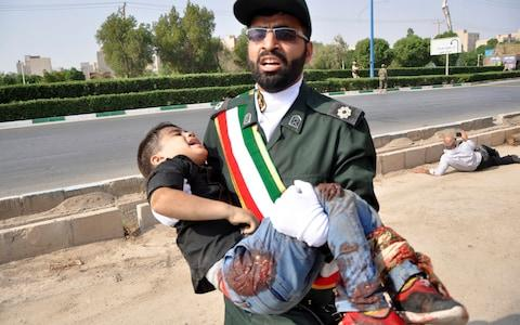 A Revolutionary Guard member carries a wounded boy after a shooting during a military parade - Credit: AP