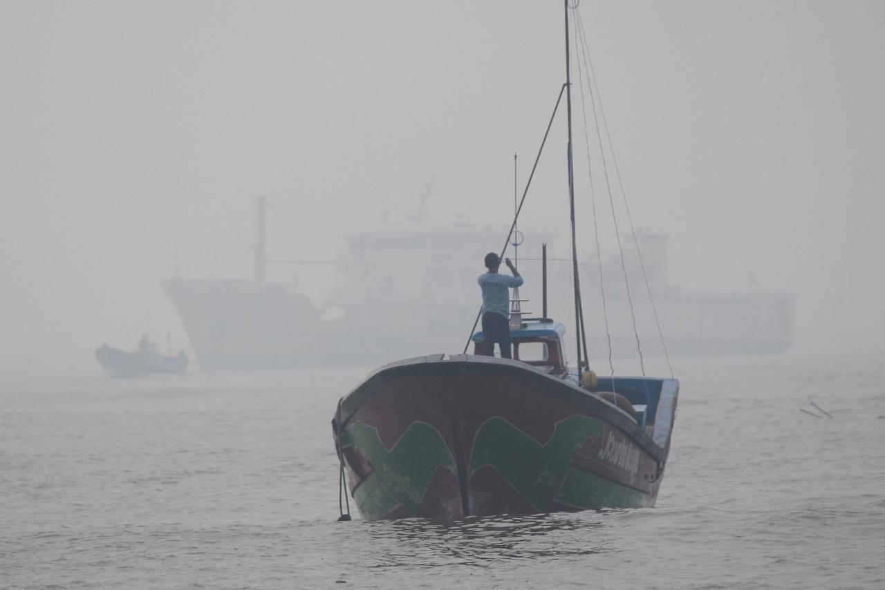 A man stands on a wooden boat during a haze produced by peatland fires at Meulaboh port, in Aceh Barat, Aceh province, Indonesia July 27, 2017 in this photo taken by Antara Foto. Antara Foto/Syifa Yulinnas via REUTERS. ATTENTION EDITORS - THIS IMAGE WAS PROVIDED BY A THIRD PARTY. MANDATORY CREDIT. INDONESIA OUT. NO COMMERCIAL OR EDITORIAL SALES IN INDONESIA.