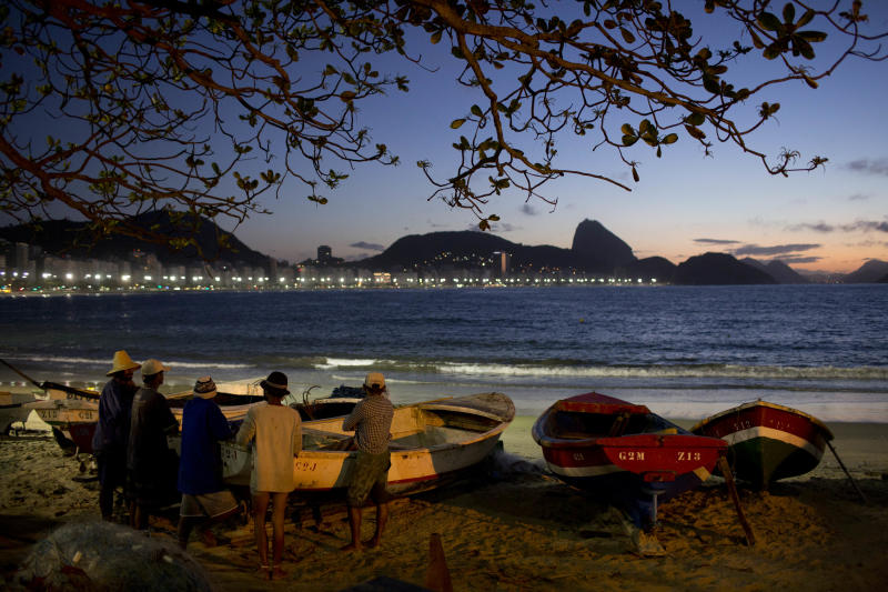 In this Aug. 21, 2013 photo, fishermen and helpers gather before sunrise on Copacabana beach in Rio de Janeiro, Brazil. It's just another work day on the ocean for the four score men manning the two dozen vessels that head out to try their luck six days a week. (AP Photo/Felipe Dana)