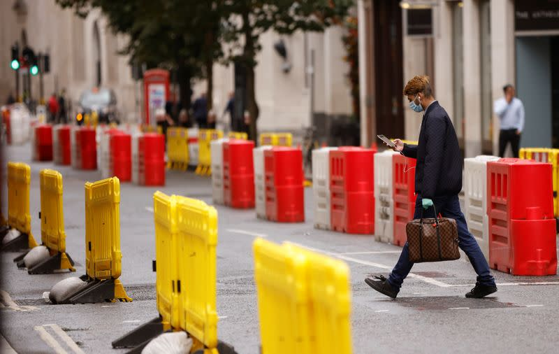 A man wearing a face mask crosses a road laid out with social distancing barriers in the City of London financial district amid the outbreak of the coronavirus disease (COVID-19)