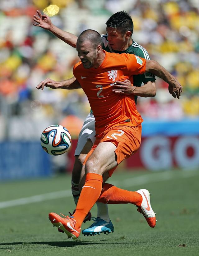 Netherlands' Ron Vlaar, front, holds off Mexico's Oribe Peralta during the World Cup round of 16 soccer match between the Netherlands and Mexico at the Arena Castelao in Fortaleza, Brazil, Sunday, June 29, 2014. (AP Photo/Wong Maye-E)