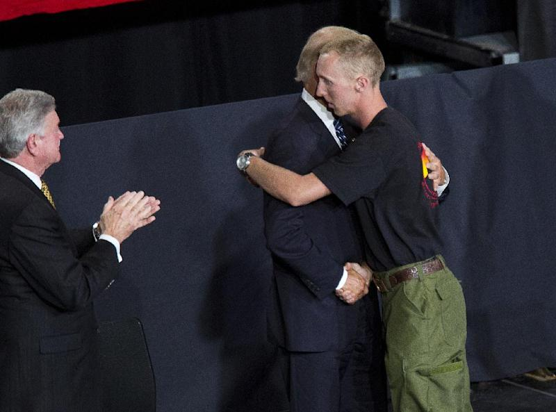 Brendan McDonough is greeted by Vice President Joe Biden during a memorial service for the 19 fallen firefighters at Tim's Toyota Center in Prescott Valley, Ariz. on Tuesday, July 9, 2013. Prescott's Granite Mountain Hotshots were overrun by smoke and fire while battling a blaze on a ridge in Yarnell, about 80 miles northwest of Phoenix on June 30, 2013. (AP Photo/The Arizona Republic, Michael Chow, Pool)