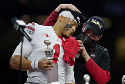 Ohio State head coach Ryan Day hugs quarterback Justin Fields after their win against Clemson in the Sugar Bowl NCAA college football game Sunday, Jan. 1, 2021, in New Orleans. Ohio State won 49-28. (AP Photo/Gerald Herbert)