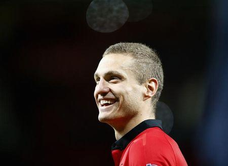 Manchester United's Vidic, who has played his final home match for team, smiles following their English Premier League soccer match against Hull City at Old Trafford in Manchester