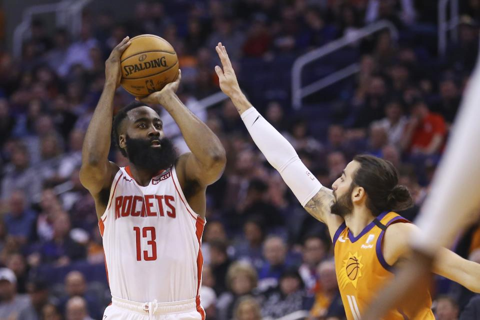 Houston Rockets guard James Harden (13) shoots a three-point basket over Phoenix Suns guard Ricky Rubio, right, during the first half of an NBA basketball game Friday, Feb. 7, 2020, in Phoenix. (AP Photo/Ross D. Franklin)