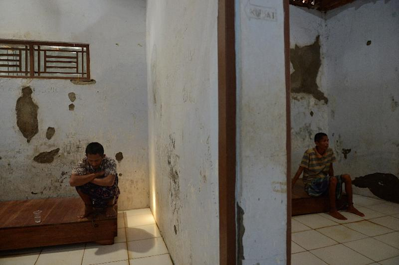 Indonesians Gunawan (L) and Sholeh (R), who suffer from mental illness, sit in their rooms at the Bina Lestari Mandiri healing center in Brebes (AFP Photo/Adek Berry)