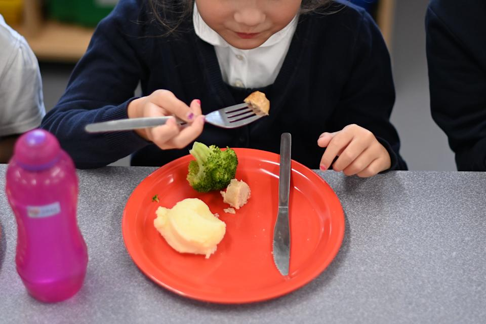 A pupil eats her cooked hot dinner during her lunch break in the canteen at St Luke's Church of England Primary School in East London on September 3, 2020. - Pupils in Britain have on Thursday begun to return to schools for the first time since they were all closed in March, due to the COVID-19 pandemic. (Photo by DANIEL LEAL-OLIVAS / AFP) (Photo by DANIEL LEAL-OLIVAS/AFP via Getty Images)