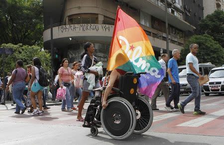 A handicapped person carries a campaign flag for President Dilma Rousseff who will face rival Senator Aecio Neves in the runoff presidential election on Sunday, in downtown Belo Horizonte, October 21, 2014. REUTERS/Washington Alves