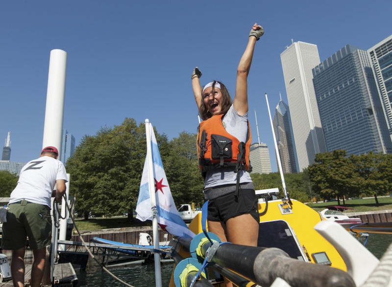 Jenn Gibbons celebrates as she completes a 1,500 mile rowing trip around Lake Michigan to raise money for an organization helping cancer survivors on Tuesday, Aug. 14, 2012 in Chicago. (AP Photo/Sitthixay Ditthavong)