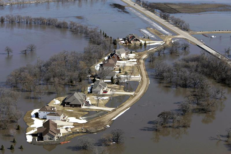 In this March 21, 2010 file photo, a subdivision is surrounded by flood waters from the swollen Red River in south of Fargo, N.D. Federal Emergency Management Agency officials are frustrated by the number of people in the Red River Valley and elsewhere in North Dakota who don't have flood insurance, citing the state's history of presidential disaster declarations. The number of insurance policies in flood-prone Fargo and Cass County, where residents have battled flooding along the Red River and its tributaries for six of the last eight years, dropped by more than 40 percent from 2011 to 2012, FEMA officials said. (AP Photo/M. Spencer Green)