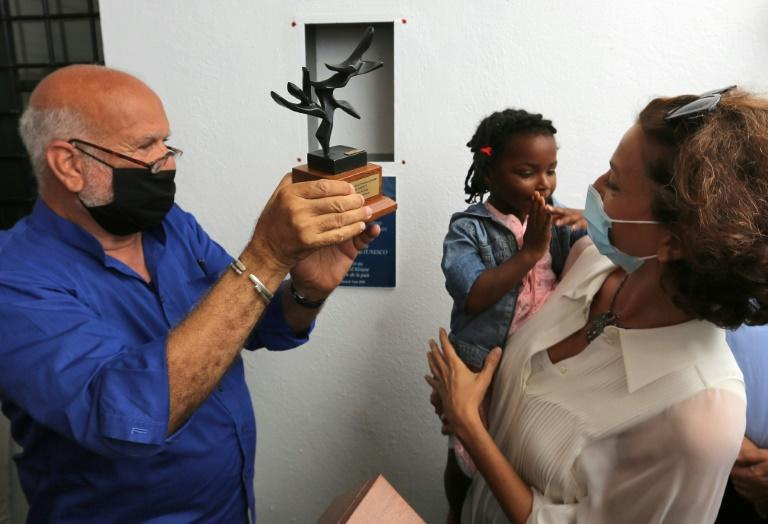 Azoulay is pictured holding the child of a migrant next to Algerian artist Koraichi during her visit