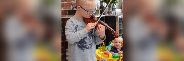Robert playing the violin for his baby brother.