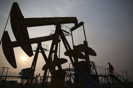 A worker examines a pumpjack at a PetroChina oil field in Panjin