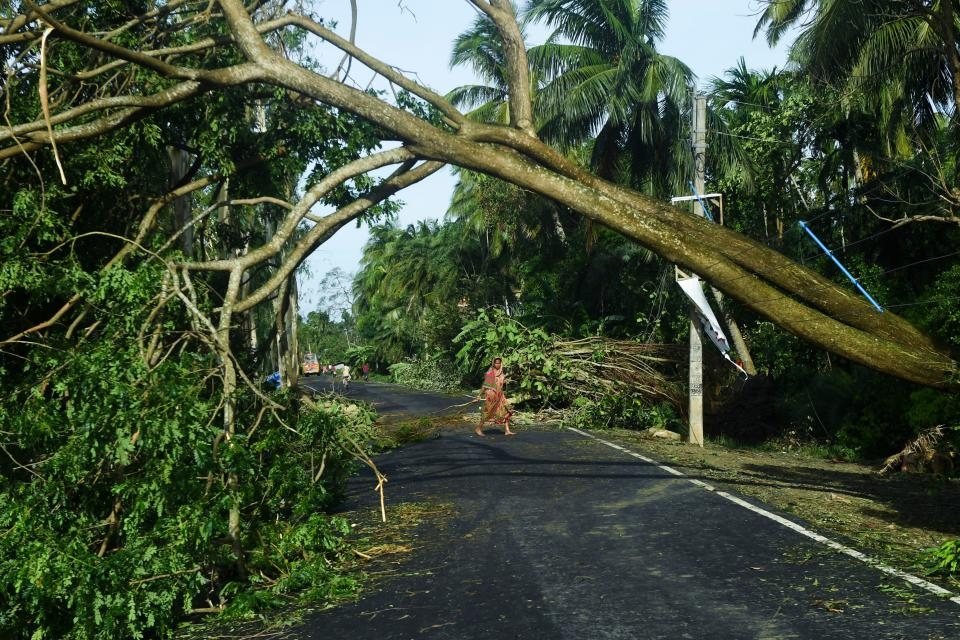 A woman removes debris from a road after the landfall of cyclone Amphan in Midnapore, West Bengal, on May 21, 2020. (Photo by DIBYANGSHU SARKAR/AFP via Getty Images)