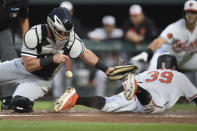 Chicago White Sox catcher James McCann loses the ball as Baltimore Orioles' Renato Nunez slides safely across the plate on a RBI-single by Rio Ruiz in the first inning of a baseball game, Wednesday, April 24, 2019, in Baltimore. (AP Photo/Gail Burton)