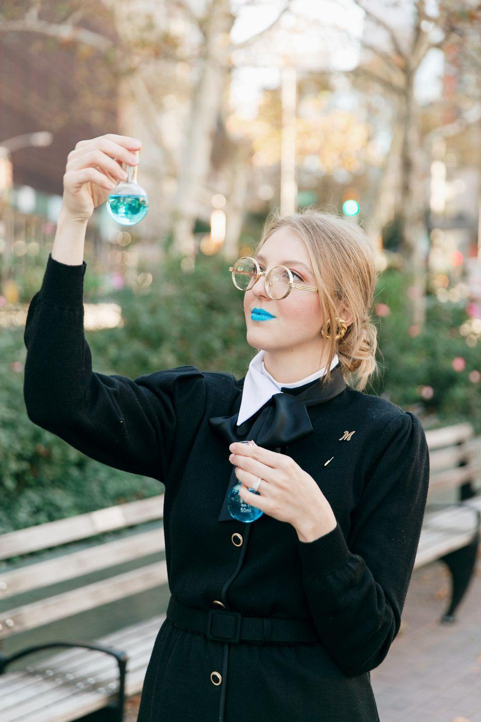 """<p>Here's a fun tribute to French physicist and chemist Marie Curie. If you've got a black dress and a few neon accessories (so as to highlight each of them in a flashy way!), you'll be good to go. And if you don't have any blue food coloring for your """"lab chemicals,"""" you can always opt for a blue-colored sports drink! </p><p><a class=""""link rapid-noclick-resp"""" href=""""https://www.amazon.com/NYX-Macaron-Pastel-Lippies-Lipstick/dp/B00K4EIIEC?tag=syn-yahoo-20&ascsubtag=%5Bartid%7C10050.g.4571%5Bsrc%7Cyahoo-us"""" rel=""""nofollow noopener"""" target=""""_blank"""" data-ylk=""""slk:SHOP BLUE LIPSTICK"""">SHOP BLUE LIPSTICK</a> </p>"""