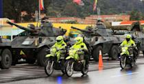 Riot police officers ride past army tanks on the outskirts of Bogota on May 4, 2021