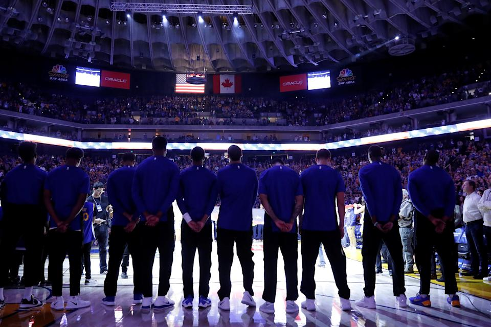 Members of the Golden State Warriors stand during the national anthem before their NBA pre-season game against the Denver Nuggets at Oracle Arena in Oakland, California, U.S., September 30, 2017. REUTERS/Stephen Lam