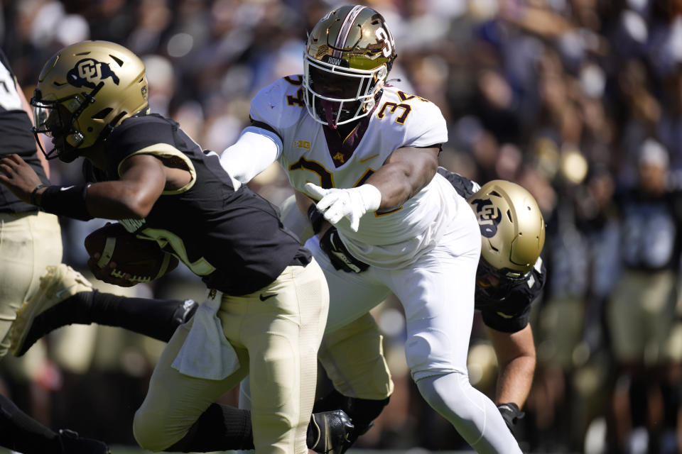 Minnesota defensive lineman Boye Mafe, right, reaches out to tackle Colorado quarterback Brendon Lewis in the first half of an NCAA college football game Saturday, Sept. 18, 2021, in Boulder, Colo. (AP Photo/David Zalubowski)