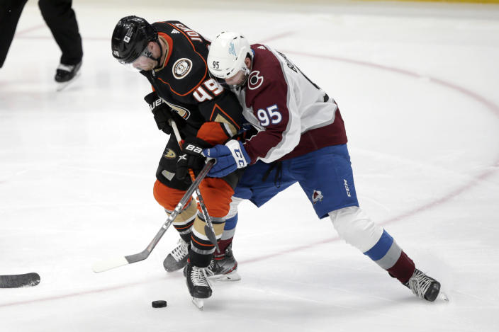 Anaheim Ducks left wing Max Jones, left, competes for the puck with Colorado Avalanche left wing Andre Burakovsky during the third period of an NHL hockey game in Anaheim, Calif., Sunday, Jan. 24, 2021. (AP Photo/Alex Gallardo)