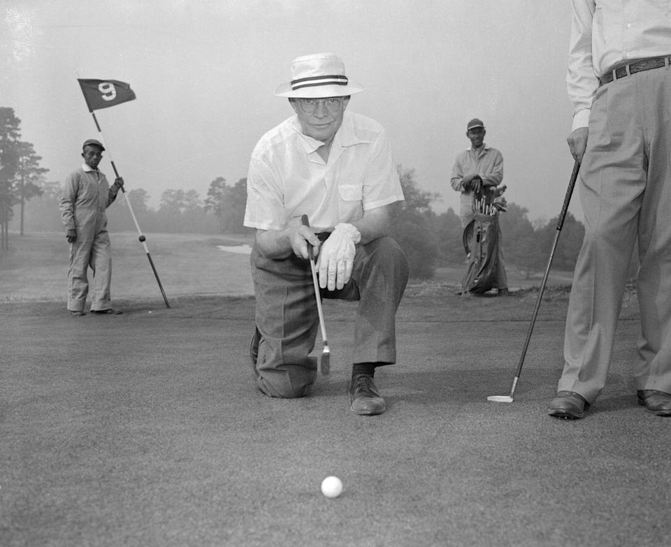 <p>Dwight Eisenhower lines up a putt while golfing in 1953. </p>