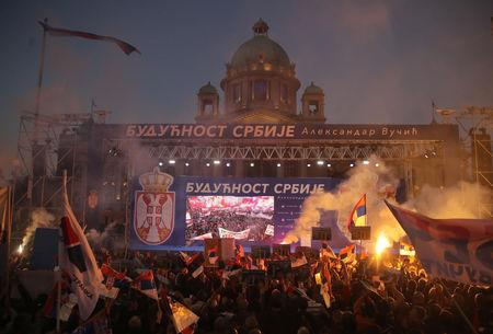 "Supporters of Serbian President Aleksandar Vucic burn flare as they wait for his arrival for his campaign rally ""The Future of Serbia"" in front of the Parliament Building in Belgrade, Serbia, April 19, 2019. REUTERS/Marko Djurica. The Banner reads: ""The future of Serbia""."