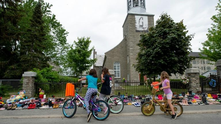 Local children of Kahnawake, Quebec stop to view the hundreds of children's shoes placed in front of the St. Francis Xavier Church, in tribute to a mass grave of 215 Indigenous children found at the residential school in British Columbia, Canada