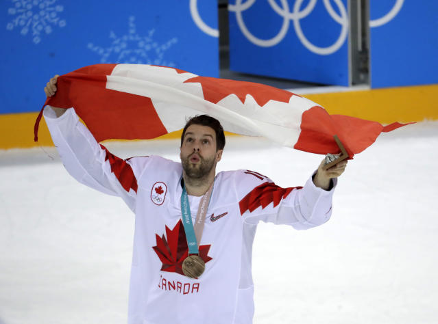 Chris Kelly (11), of Canada, waves a flag as he celebrate after beating the Czech Republic in the men's bronze medal hockey game at the 2018 Winter Olympics in Gangneung, South Korea, Saturday, Feb. 24, 2018. (AP Photo/Julio Cortez)