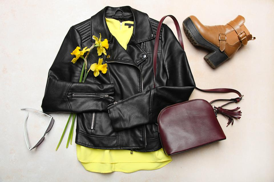 Stylish fashionable black leather jacket, spring boots and small bag on neutral background. Concept outerwear, spring clothes. Top view.