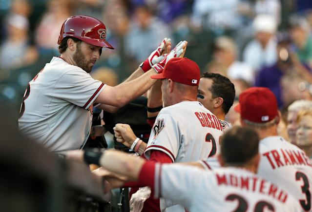 Arizona Diamondbacks' Nick Evans, left, is congratulated after hitting a solo home run by manager Kirk Gibson against the Colorado Rockies in the fourth inning of a baseball game in Denver on Tuesday, June 3, 2014. (AP Photo/David Zalubowski)