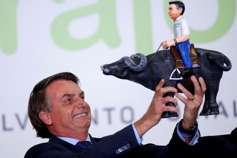Brazil's President Jair Bolsonaro holds a doll depicting him riding a toy buffalo during a ceremony at the Planalto Palace in Brasilia, Brazil March 3, 2020. REUTERS/Adriano Machado     TPX IMAGES OF THE DAY