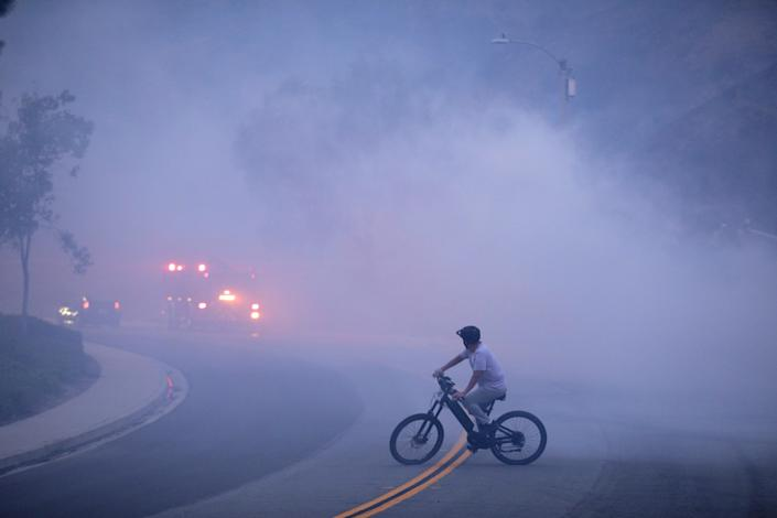A bicyclist pauses in a roadway, looking at a fire truck whose lights are visible in the smoky gloom.