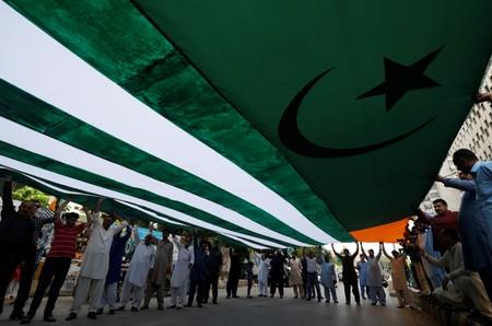 People carry an Azad Kashmir's flag as they listen to the speeches of the local political activists from Jammu & Kashmir Youth Forum, over India's decision to revoke the special status of Jammu and Kashmir, during a protest in Karachi